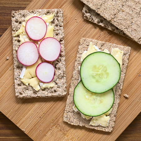 Wholemeal rye crispbread with brie cheese, radish and cucumber slices, photographed overhead with natural light