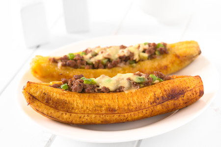 Baked ripe plantain stuffed with mincemeat, olive, green bell pepper and onion, sprinkled with cheese, a traditional dish in Central America called Canoa de Platano (Plantain Canoe), photographed with natural light (Selective Focus, Focus on the middle fr