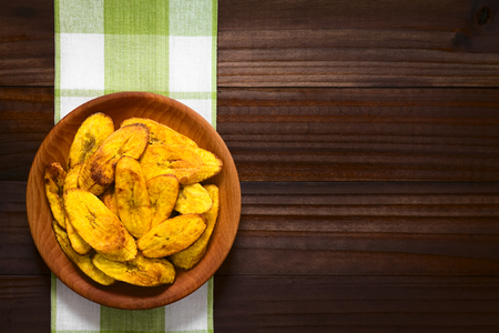 Fried slices of ripe plantains, a traditional and popular snack and accompaniment in Central America and Northern South America, photographed overhead on dark wood with natural light  Stockfoto
