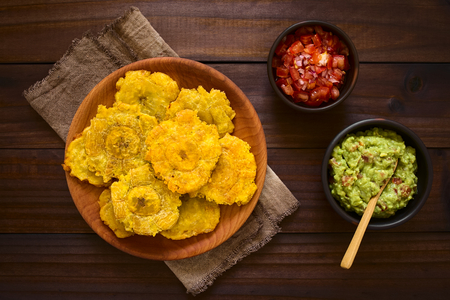 Patacon or toston, fried and flattened pieces of green plantains, a traditional snack or accompaniment in the Caribbean, guacamole and tomato and onion salad on the side, photographed overhead on dark wood with natural light