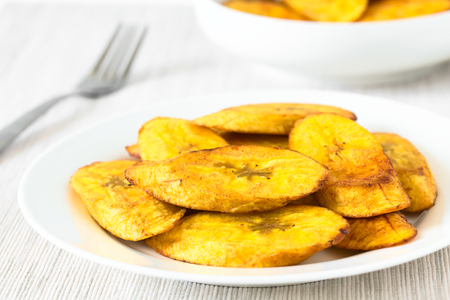northern light: Fried slices of ripe plantains, a traditional and popular snack and accompaniment in Central America and Northern South America, photographed with natural light (Selective Focus, Focus on the front of the top slice)