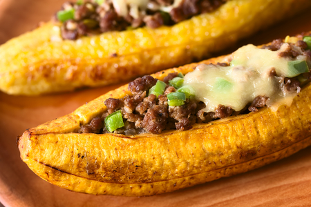 Baked ripe plantain stuffed with mincemeat, olive, green bell pepper and onion, sprinkled with cheese, a traditional dish in Central America called Canoa de Platano (Plantain Canoe), photographed with natural light (Selective Focus, Focus in the middle of the image)