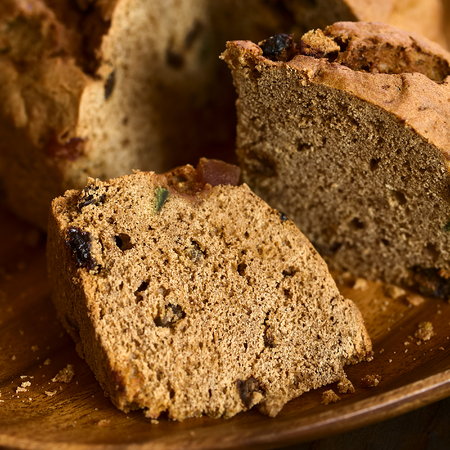 Traditional Chilean Pan de Pascua Christmas Cake made with spices, dried fruits and raisins, photographed with natural light (Selective Focus, Focus diagonally through the slice in the front) Stock Photo