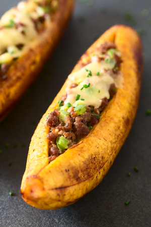 creole: Baked ripe plantain stuffed with mincemeat, olive, green bell pepper and onion, cheese on top, sprinkled with chives, a traditional dish in Central America called Canoa de Platano (Plantain Canoe), photographed on slate with natural light (Selective Focus, Focus one third into the plantain)