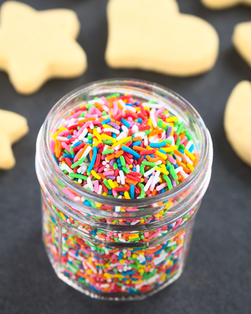 Colorful sugar sprinkles in glass jar with undecorated sugar cookies in the back, photographed on slate (Selective Focus, Focus one third into the sprinkles)