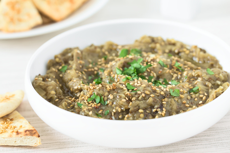 Homemade roasted eggplant dip or spread, baba ganoush in the Mediterranean cuisine, with olive oil, sesame and parsley on top, homemade sesame pita chips on the side, photographed with natural light (Selective Focus, Focus one third into the dip) Stock fotó