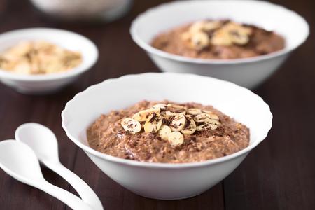 トーストしたアーモンドスライスとすりおろしたチョコレートを上に置いたチョコレートオートミールまたはオート麦のおかゆを小さなボウルに盛