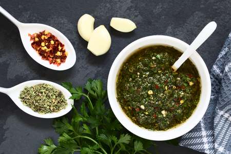 Raw homemade Argentinian green Chimichurri or Chimmichurri salsa or sauce made of parsley, garlic, oregano, hot pepper, olive oil, vinegar, served in bowl, photographed overhead on slate with natural light (Selective Focus, Focus on the salsa) Imagens - 96109868