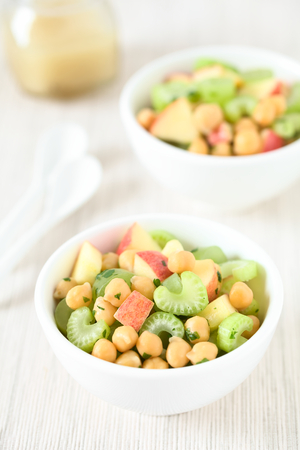 Fresh vegan chickpea, celery, grape and apple salad with parsley in bowls, photographed with natural light (Selective Focus, Focus in the middle of the first salad) Archivio Fotografico - 96109870