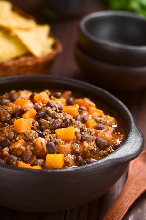 Homemade chili con carne with mincemeat, red and black beans, tomato sauce and pumpkin in rustic bowl with tortilla chips in the back (Selective Focus, Focus in the middle of the dish) Foto de archivo