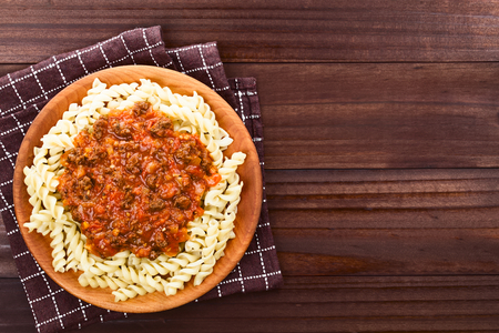 Homemade vegan bolognese sauce made with soy meat, fresh tomatoes, onion and garlic served on fusilli pasta on wooden plate, photographed overhead with copy space on the right side