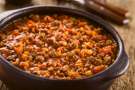 Homemade vegan bolognese sauce made with soy meat, fresh tomatoes, onion and garlic, served in rustic bowl (Selective Focus, Focus one third into the sauce)