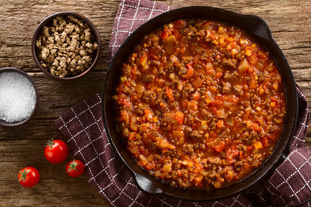 Homemade vegan bolognese sauce made with soy meat, fresh tomatoes, onion and garlic, served in cast iron skillet, photographed overhead on rustic wood