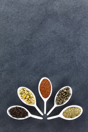 A variety of loose dried tea leaves on spoons (black, chamomile, rooibos, green and mate tea), photographed overhead on slate with copy space on the top