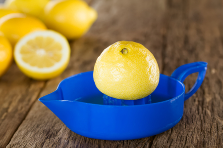 Lemon half on blue lemon or citrus squeezer with lemons in the back, photographed on wood (Selective Focus, Focus on the tip of the lemon half on the squeezer)