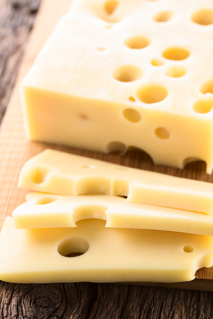 Piece and slices of Emmental, Emmentaler or Emmenthal cheese on wooden cutting board (Selective Focus, Focus one third into the image) Stockfoto