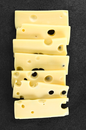 Slices of Emmental, Emmentaler or Emmenthal cheese, photographed overhead on slate