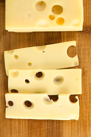 Piece and slices of Emmental, Emmentaler or Emmenthal cheese, photographed overhead on wood (Selective Focus, Focus on the slices) Stockfoto