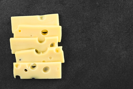 Slices of Emmental, Emmentaler or Emmenthal cheese on slate, photographed overhead with copy space on the right side Stockfoto