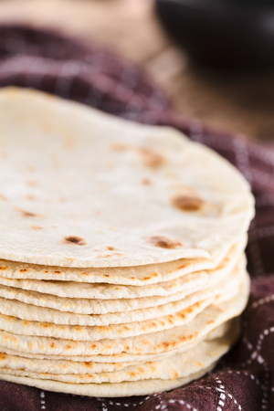 Fresh homemade flour tortillas on kitchen towel (Selective Focus, Focus on the front of the tortillas)