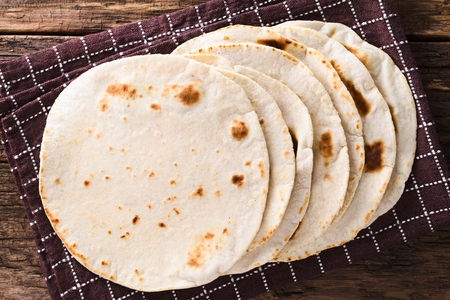 Fresh homemade flour tortillas on kitchen towel, photographed overhead