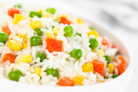 Cooked white rice mixed with colorful vegetables (onion, carrot, green peas, corn, green beans) in white bowl (Selective Focus, Focus in the middle of the image)