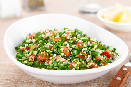 Fresh vegan Tabbouleh salad made of tomato, parsley, onion and couscous in bowl (Selective Focus, Focus one third into the salad)