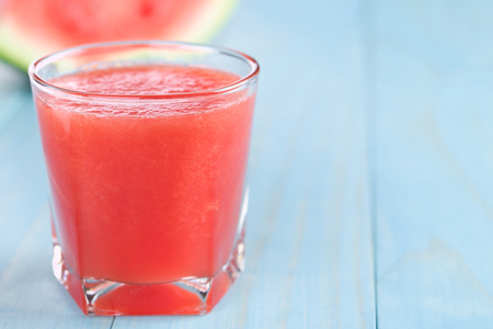 Refreshing watermelon juice on blue wood, copy space on the right side (Selective Focus, Focus on the front of the glass rim) Stockfoto