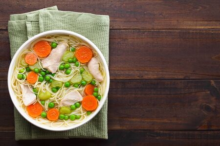 Fresh homemade chicken noodle soup with carrot, peas and celery in white soup bowl, photographed overhead with copy space on the side