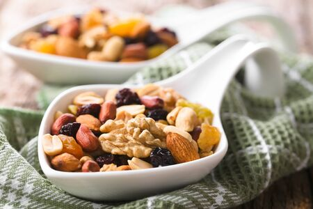 Healthy trail mix snack made of nuts (walnut, almond, peanut) and dried fruits (raisin, sultana) on spoons (Selective Focus, Focus one third into the first spoon)