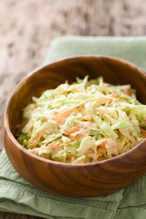 Coleslaw made of freshly shredded white cabbage and grated carrot with homemade mayonnaise-based salad dressing in wooden bowl (Selective Focus, Focus one third into the salad) Imagens