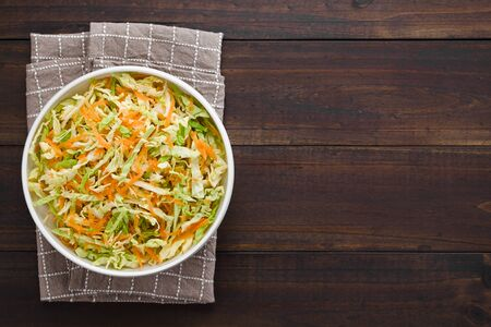 Coleslaw made of freshly shredded white cabbage and grated carrot served in bowl, photographed overhead with copy space on the right side (Selective Focus, Focus on the salad) Imagens