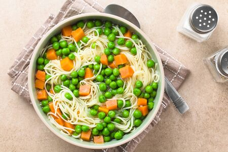 Fresh homemade vegetable noodle soup with carrot, peas, onion and angel hair pasta in soup bowl, photographed overhead with spoon, salt and pepper on the side (Selective Focus, Focus on the soup) Imagens