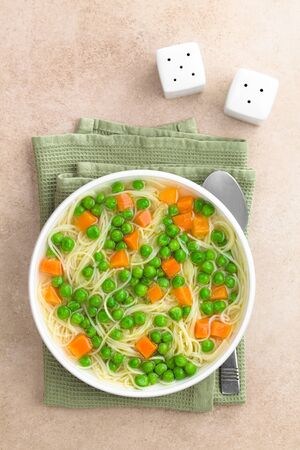 Fresh homemade vegetable noodle soup with carrot, peas, onion and angel hair pasta in white soup bowl, photographed overhead with spoon, salt and pepper on the side (Selective Focus, Focus on the soup)