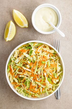 Coleslaw made of freshly shredded white cabbage and grated carrot with homemade mayonnaise-based salad dressing and lemon wedges on the side, photographed overhead (Selective Focus, Focus on the salad) Imagens