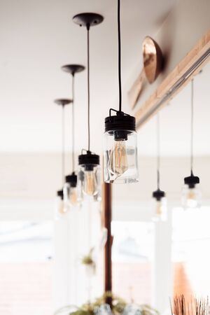 Four brass modern industiral ceiling lights hanging in front of the mirrow and reflecting in it Stock Photo