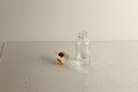 Clear glass bottle with medicine pipette on white background with water drops