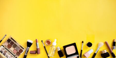 Make up flat lay on yellow background. Web banner with cosmetics accessories.