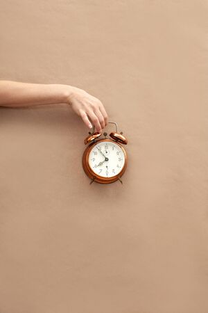 Hand holding bronze watch on brown paper background.