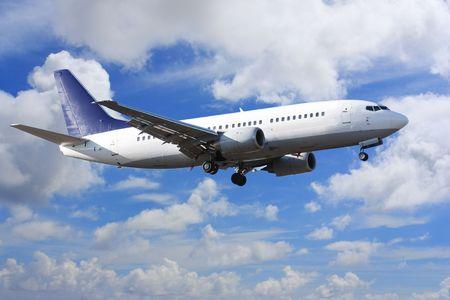 passenger vehicle: Jet airplane landing in bright cloudy sky Stock Photo