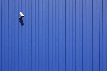 security camera on blue metallic wall with copy space photo