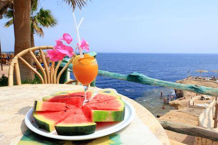juice bar: Orange cocktail on table, sharm sea in background