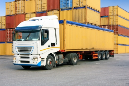 container port: truck waiting in commercial harbor area, containers in background Stock Photo