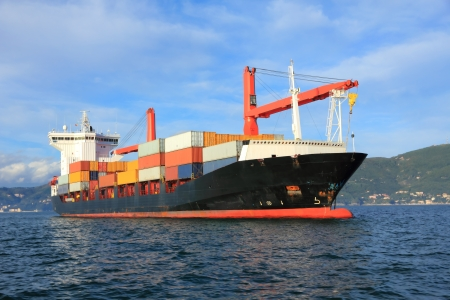 loading cargo: container cargo ship arriving in harbor Stock Photo