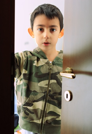 see through: little child looking serious through the door