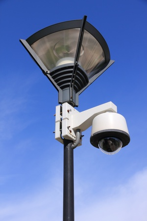 security camera on street lamp over blue sky photo
