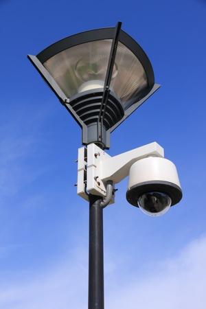 city surveillance: security camera on street lamp over blue sky Stock Photo