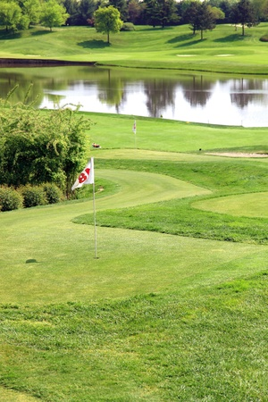 golf field with flag and artificial lake in background photo