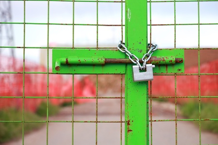 green construction site gate closed with chain and padlock photo