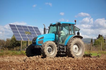 arando: agricultura, tractor trabajando en un campo con panel de solar fotovoltaica en segundo plano Foto de archivo